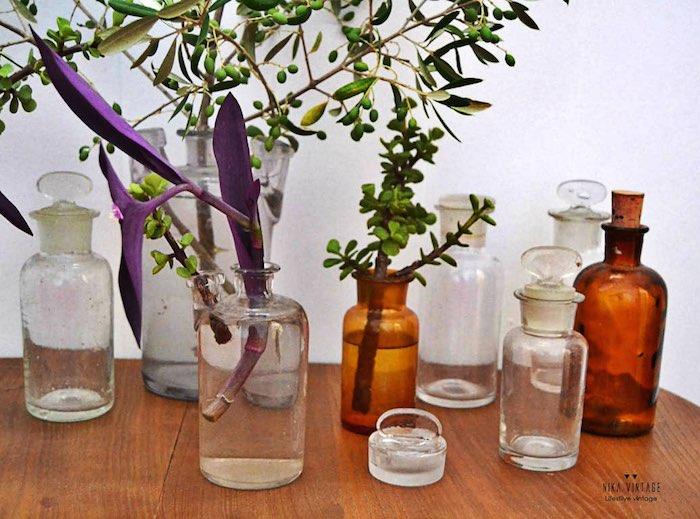 botellas de farmacia con flores, ramas y adornos florales