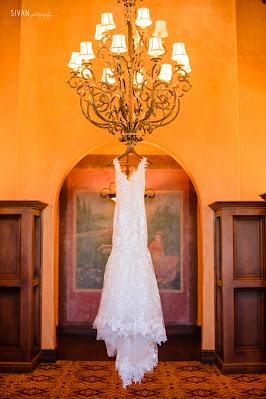 wedding dress hanging from chandelier