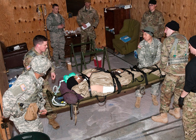 military students look at a patient on a gurny in a shelter