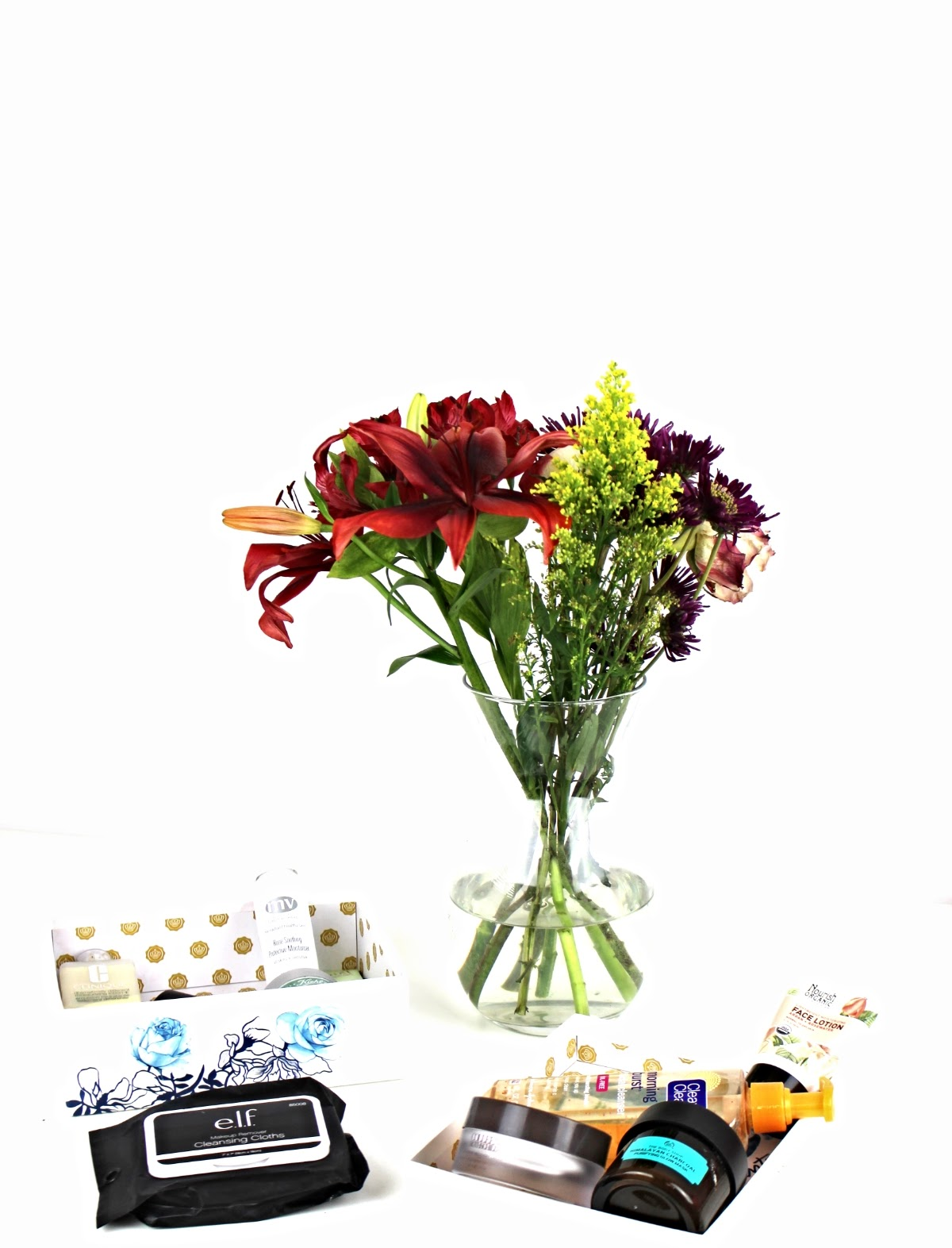 This is a photo of a beautiful flower bouquet, alongside all my favorite winter skin care products including Kiehl's, Kate Somerville, Colleen Rothschild, and many more!