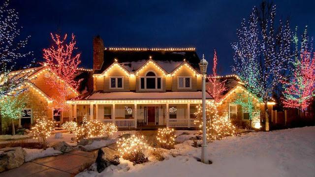 Kerst wallpaper met huis volgehangen met gekleurde lichtjes.