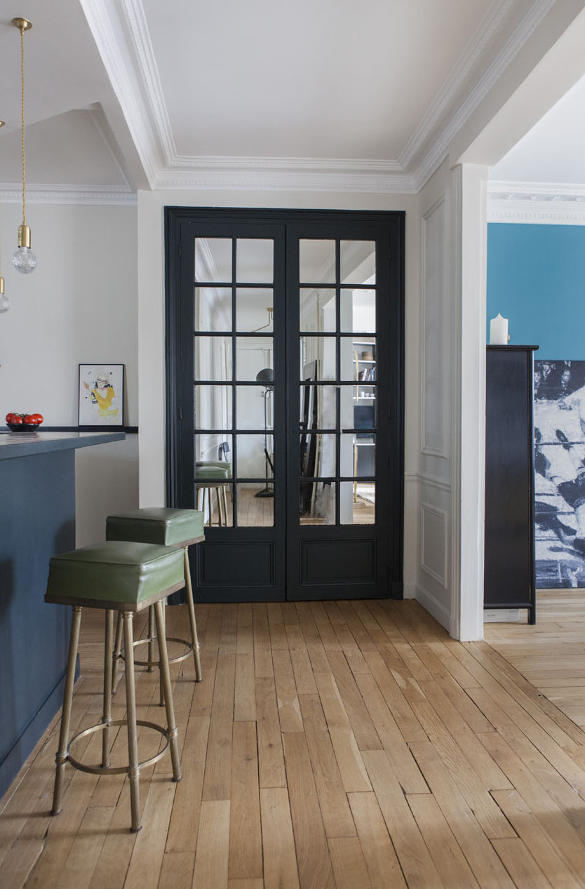 paris apartment with teal color, mid century modern furniture, large double doors, kitchen stools