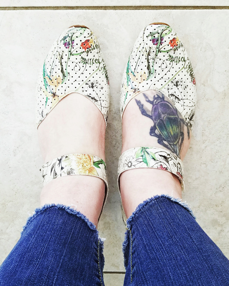image of my lower calves and feet; I am wearing blue jeans with raw cuffs and Mary Jane style shoes in white with a colorful floral pattern; the beetle tattoo on my right foot is visible in the opening below the strap