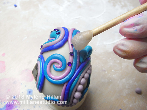 Epoxy resin clay covered egg being decorated with Swarovski crystals