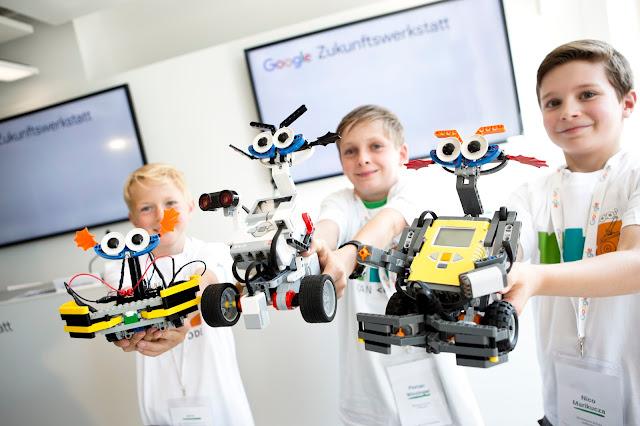 Foto von Schülern, die einen selbst gebastelten Roboter in die Kamera halten.