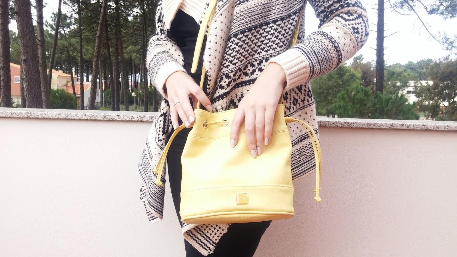 Look do dia com predominância da cor preta e apontamentos roxos e amarelos.