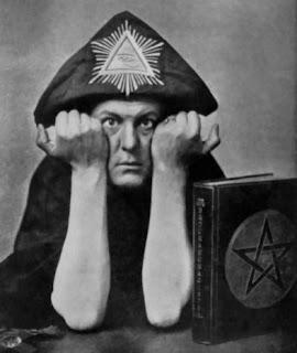 aleister crowley con pirámide en la cabeza y libro satánico