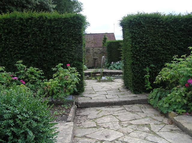 kamienna ścieżka w ogrodzie, ogród angielski, żywopłoty z cisa