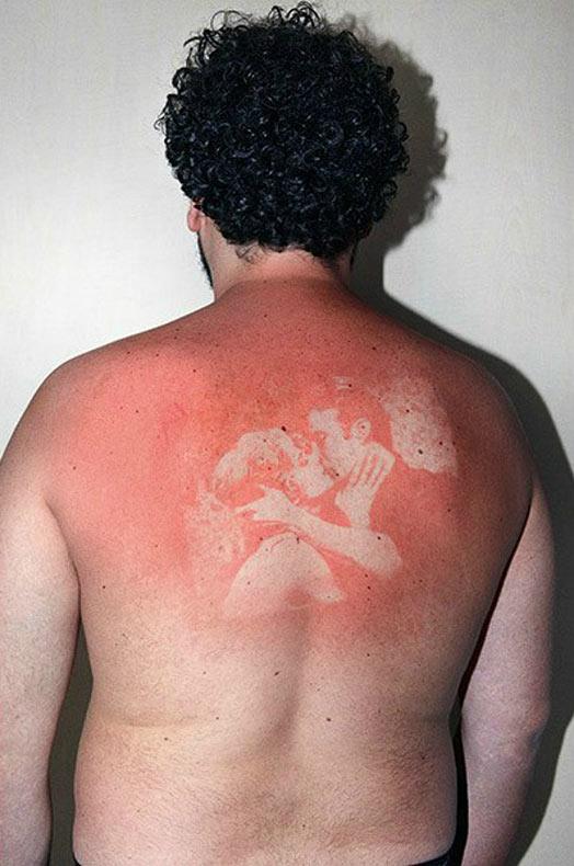 Artista maneja una lámpara UV para inventar impresiones de imagenes sobre la piel bronceada