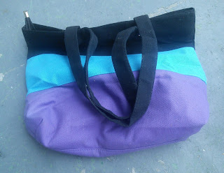A bag striped in Purple, Turquoise, and Black.  It has two handles and a zippered top.