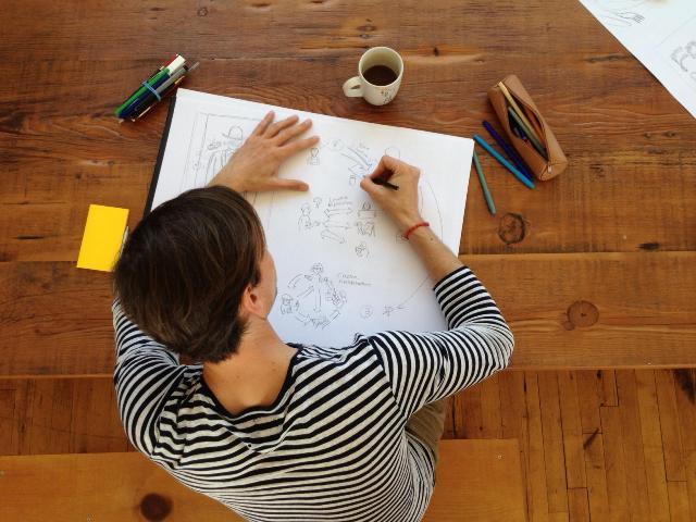 Definir el curso de la vida : toma cenital de hombre con camisa rayada dibujando esquemas sobre mesa de madera