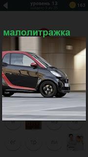 На асфальте стоит маленький автомобиль малолитражка черного цвета