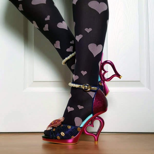 legs wearing heart print tights and purple, blue and pink metallic heart heeled shoes