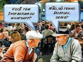 Foto em um restaurante bem amplo e lotado. Em foco dois idosos sentados lado a lado conversando, o da esquerda diz: Você tem Instagram ou WhatsApp? O outro com aparelho de audição no ouvido esquerdo responde: Não, só tenho Dorflex, serve?
