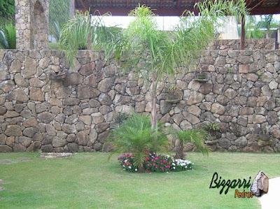 Construção de muro de pedra com pedra bruta deixando as bases de pedra para colocação de vasos de plantas no próprio muro de pedra e execução dos caminhos de pedra com pedras rústicas e o paisagismo em residência em Mairiporã-SP.
