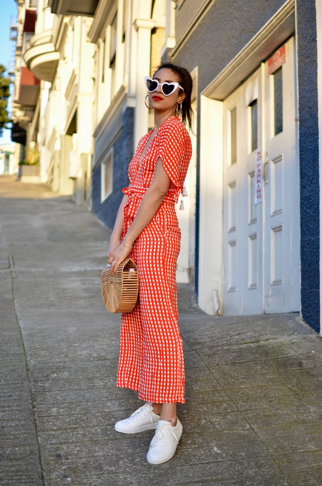 white heart cat eye shaped sunglasses, Faithfull the brand Cedric jumpsuit, red gingham jumpsuit, best red lipsticks, Banana republic white sneakers, Cult Gaia medium arc bag, Faithfull The Brand