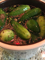 Photo of pickling cukes in crock full of brine and spices. https://trimazing.com/