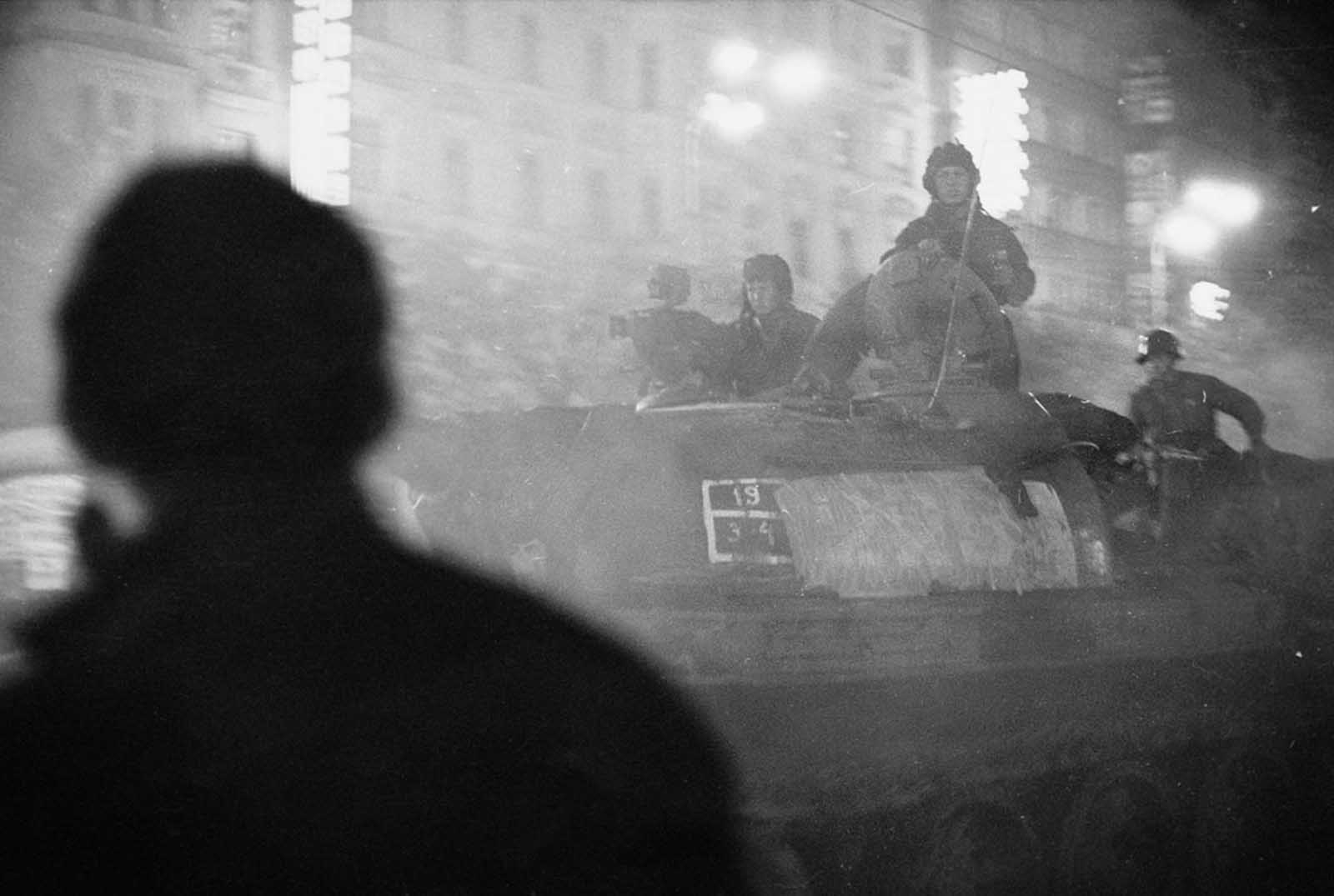 A shadowy figure watches Soviet tanks advance through the streets of Prague after nightfall in August 1968.
