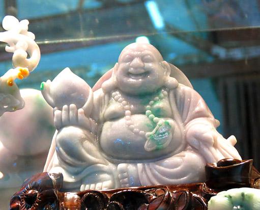 white jade Buddha sitting and laughing