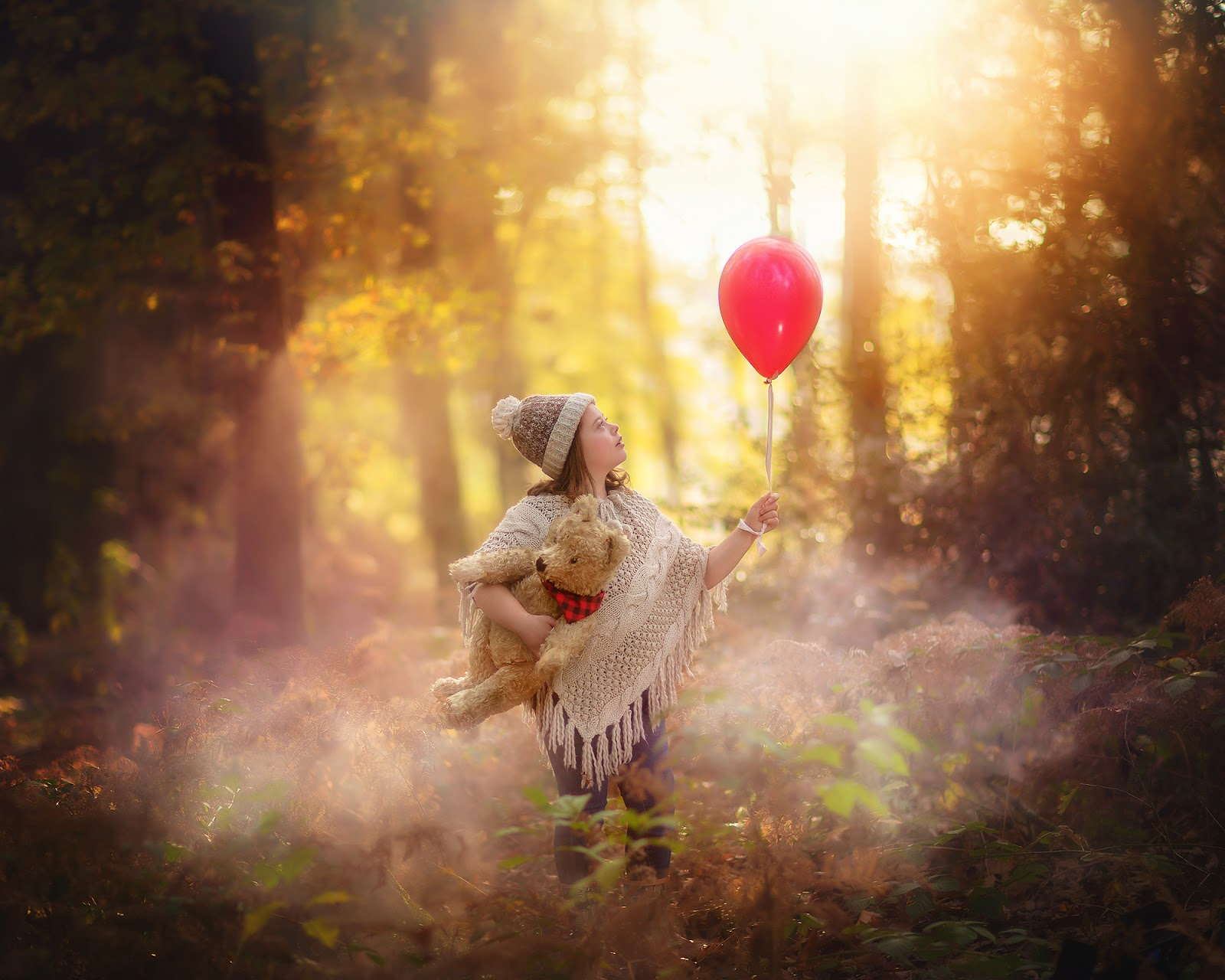 fine art autumn portrait of a child and a teddy bear holding a red balloon during sunset by Willie Kers