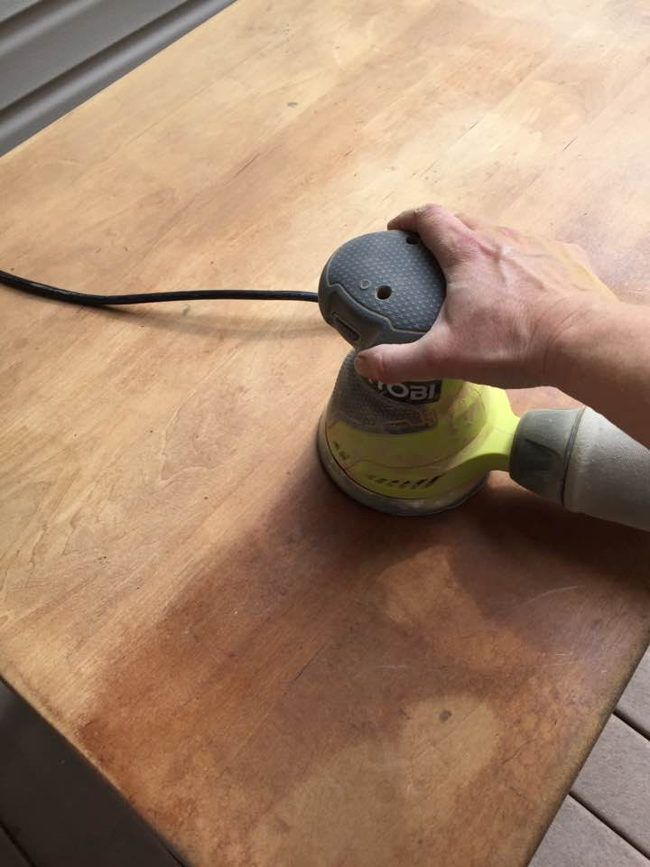 Using an orbital sander on the table top.