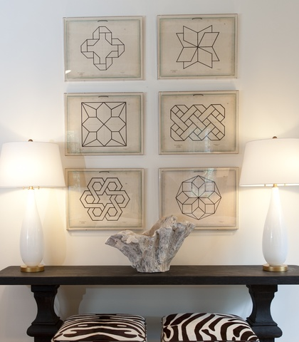 a long black accent table with two white lamps on each end and two zebra print stools sit in front of a white wall with six pictures of geometric shapes stacked on top of each other in two columns