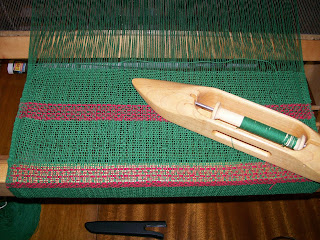 Boat shuttle and woven cloth on loom.