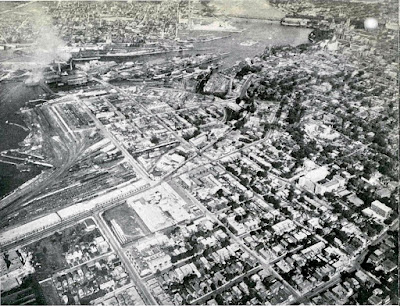 Black-and-white aerial photo taken from above Preston and Somerset with LeBreton Flats, Chaudière and Victoria Island, and Hull at left, and Somerset/Booth, Bronson/Laurier, and the Parliament buildings on the right. The Alexandra/Interprovincial bridge crosses the Ottawa River at the top. From the left near the bottom Wellington Street comes in and splits at Broad Street with Albert continuing straight and Wellington turning left at a shallow angle. On the north side of Wellington, west of Broad, is the Marine Signals building ('the longest in the British Empire') with trainyards and Nepean Bay beyond, and the blocks abutting Wellington on the South side are occupied by a few large industrial facilities. The other blocks further south are primarily residential.