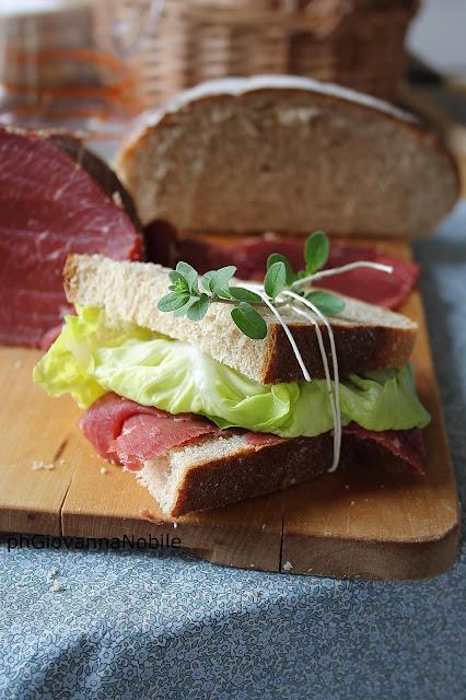 Tramezzini di pane integrale, farciti con manzo affumicato Lenti, lattuga e vinaigrette aromatica