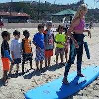 Camp Counselor and Surf Instructor Aurora Eagles giving a surfing lesson on the sand to eight Keiki Campers at Zuma Beach.