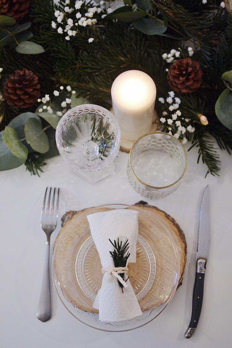 rondin de bois, centre de table avec branche de sapin, pigne de pin, feuille d'eucalyptus, bougie blanche