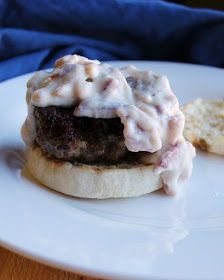 burger patty on top of english muffin bottom with creamy bacon gravy spilling off the side of the burger