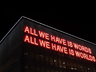 "neon sign on building that says ""All we have is words. All we have is worlds."""