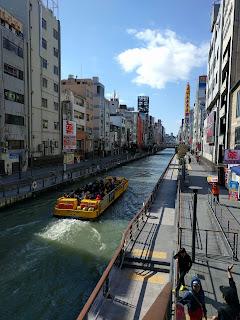 派手な黄色い観光船が行きかう道頓堀川