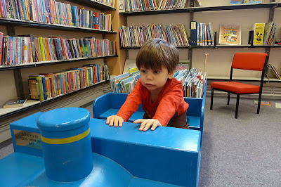 Child playing on toy train in the local library
