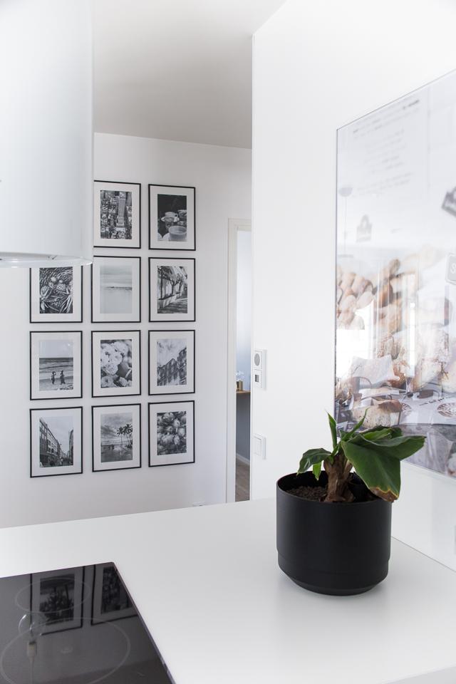 Villa H, keittiön sisustus, valokuvataulu, banaanipuu, mustavalkoiset taulut, valkoinen keittiö