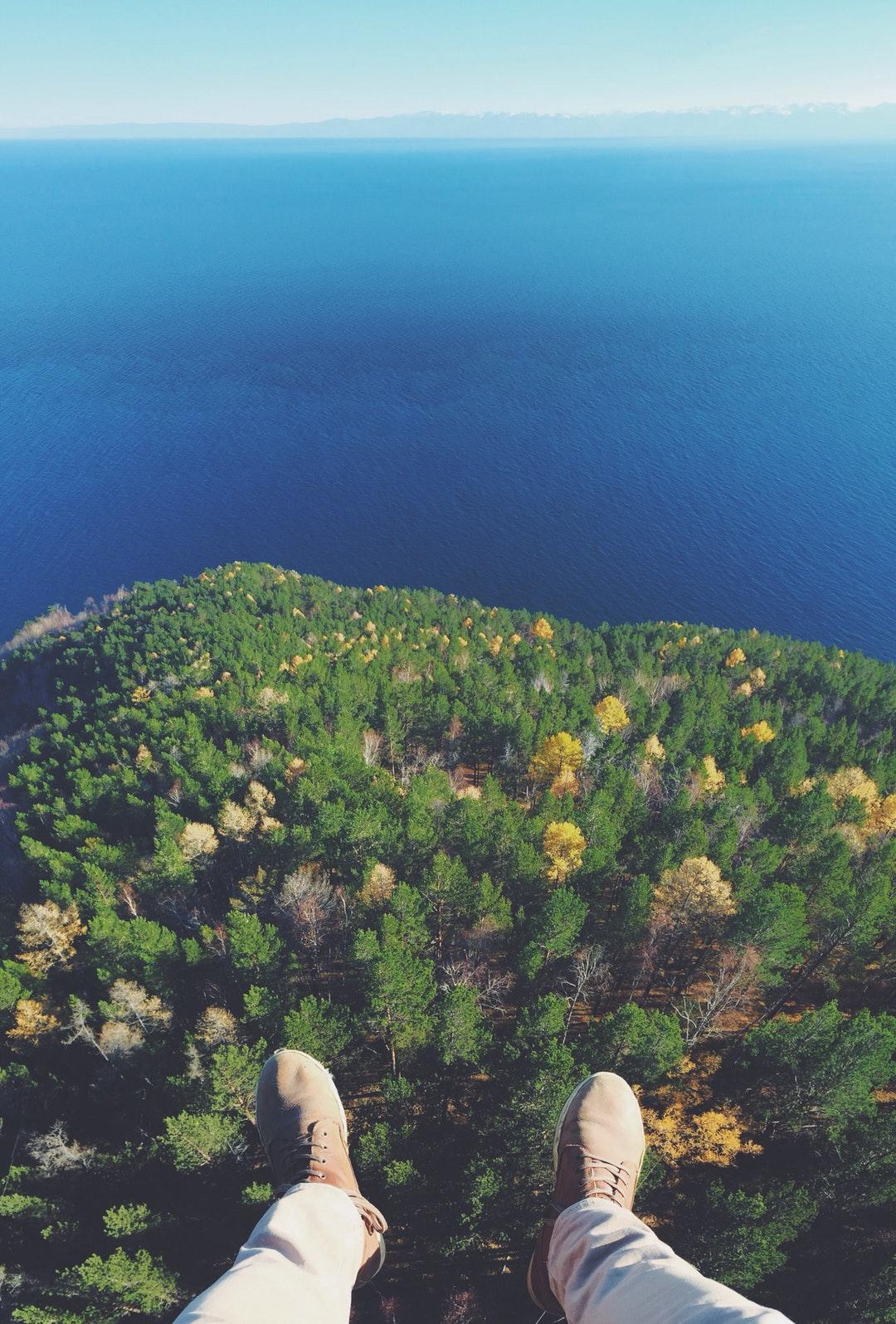 رجل يجلس فوق جبل ينظر إلي غابة خلفيات ايفون 6s