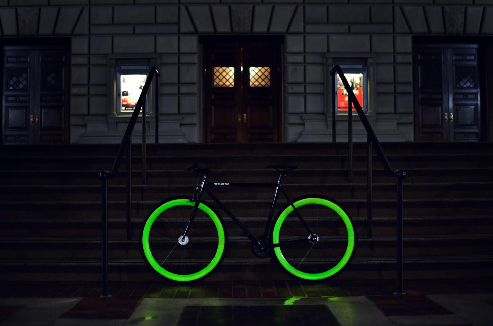 Ein Fahrrad mit leuchtenden Reifen steht vor einem Hotel