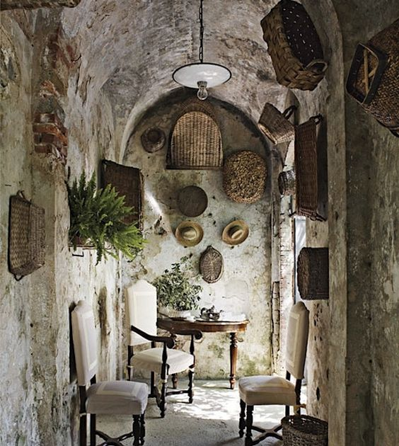 Italian farmhouse entry with arched ceiling, baskets on wall, and rustic elegance