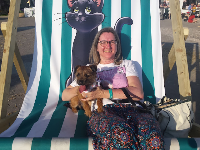 small border terrier and woman on large deckchair