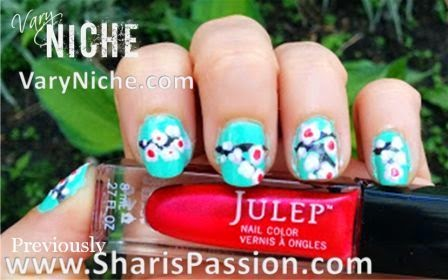 Fingernails with pale pink, white, & mauve flowers with red centers dotted over a dark brown branch running across nails with a teal background.