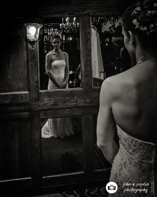 a photograph of the bride looking at herself in the mirror as she gets ready for her wedding