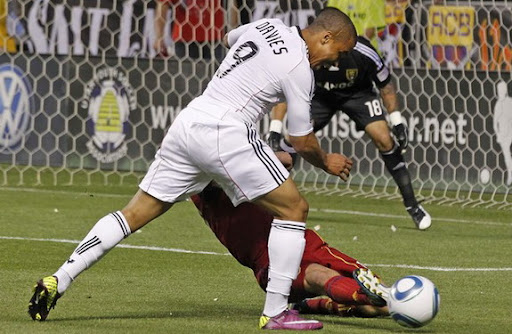 Chris Wingert kicks the ball away from Charlie Davies but was called for a penalty kick foul