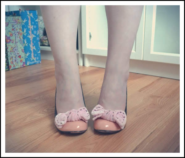feet facing forward wearing peach coloured court shoes with large velvet bow with shoe room in background