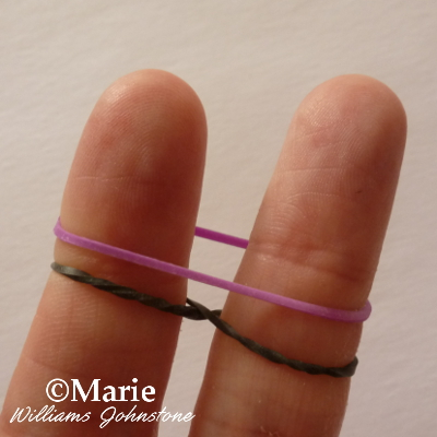 black and purple rubber bands stretched over fingers