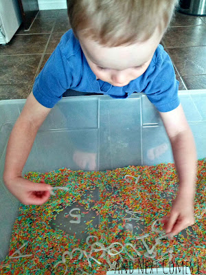 J exploring the colored rice sensory bin from And Next Comes L
