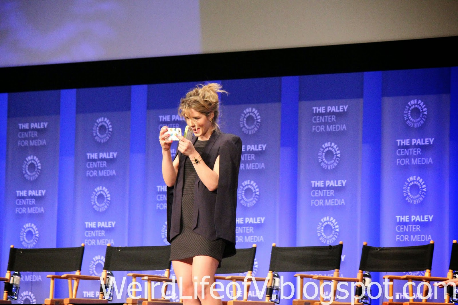 Emily Bett Rickards taking photos of the audience