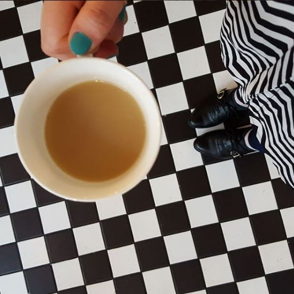 hand holding cup of tea over tiled floor
