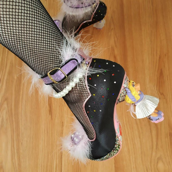 close up of foot wearing satin shoe with Miss Piggy character heel