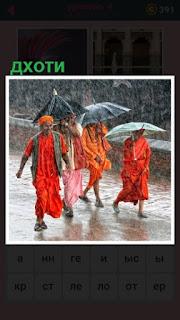 под дождем идут мужчины в дхоти с зонтом